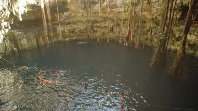 cenote at mexico. people swimming at the natural pool. a man jumping using a swing rope to the water - hole stock videos & royalty-free footage
