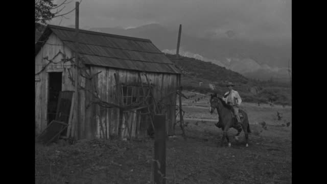 census taker carrying book on horseback rides towards ramshackle outbuilding / census taker talks to man in ragged clothes / sot unintelligible - census stock videos & royalty-free footage
