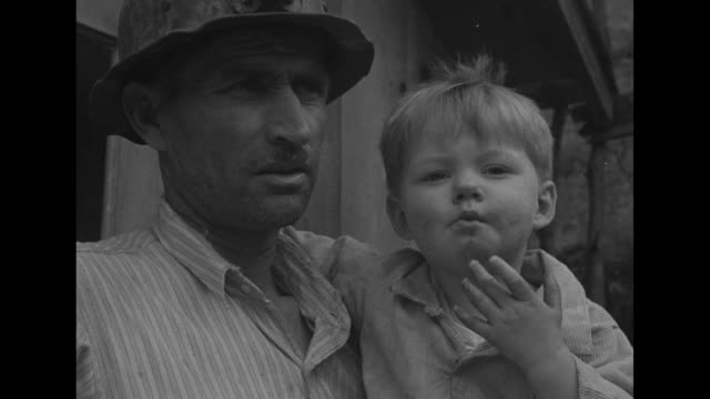 census taker climbs stairs to modest frame cabin / interviewing man wearing a miner's hat and holding a young boy as wife looks on / cu miner and... - census stock videos & royalty-free footage