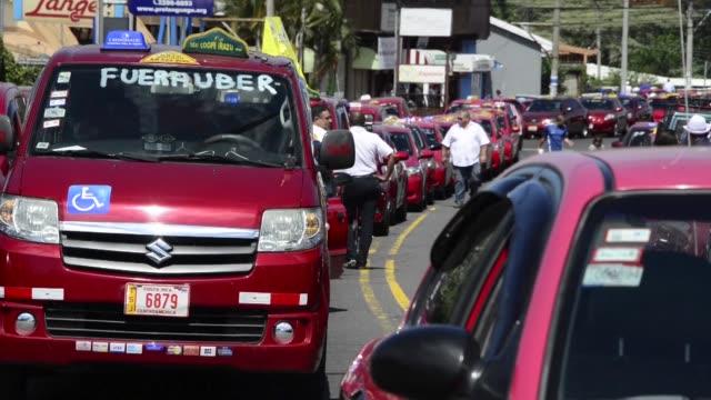 vídeos de stock e filmes b-roll de centenares de taxistas costarricenses bloquearon las calles de la capital para exigir al gobierno que bloquee uber - exigir