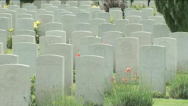 David Cameron visits memorial in Loos FRANCE Loos EXT British Prime Minister David Cameron MP walking along line of gravestones in war cemetery Ranks...