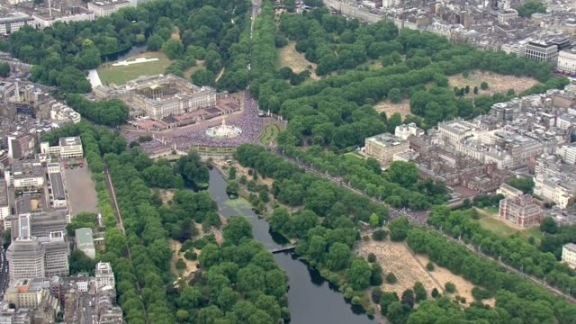 aerials ENGLAND London VIEWS / AERIALS crowds outside Buckingham Palace / Horse Guards Parade with crowds and RAF planes / St James's Park