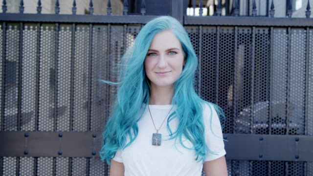 center aligned slow motion shot of a beautiful unique spunky fashionable young woman with fun cute teal blue green dyed hair standing posing outdoors in the summer - fashionable stock videos & royalty-free footage