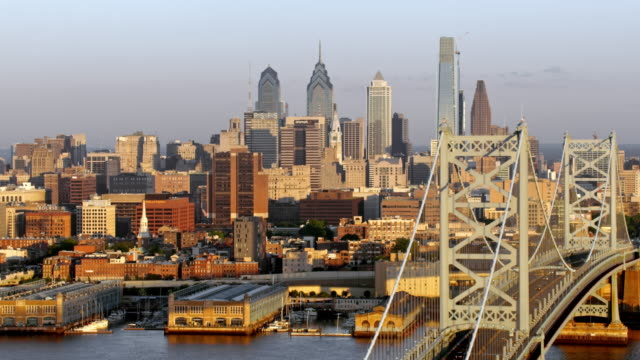 aerial center city, philadelphia and the benjamin franklin bridge across delaware river - center city philadelphia stock videos and b-roll footage