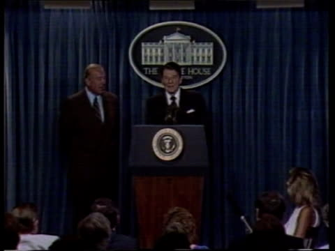 central america peace plan itn lib held in w'ton white house pres ronald reagan at podium with sec of state george shultz beside him zoom in cms... - 中央アメリカ点の映像素材/bロール
