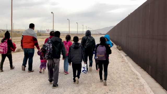 central american immigrants at the u.s.-mexico border fence on february 01, 2019 in el paso, texas. the migrants were taken into custody, seeking... - 国境の壁点の映像素材/bロール
