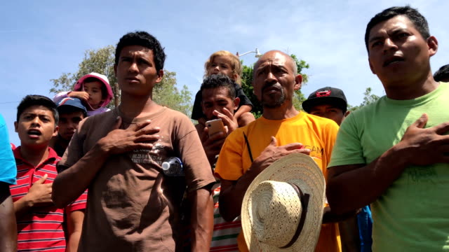 central american immigrants part of an immigrant 'caravan' sing the honduran national anthem during a protest march against us president donald trump... - 中央アメリカ点の映像素材/bロール