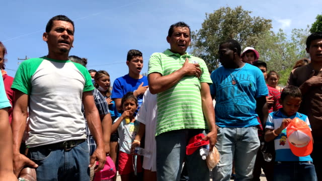 vídeos y material grabado en eventos de stock de central american immigrants part of an immigrant 'caravan' sing the honduran national anthem during a protest march against us president donald trump... - américa central