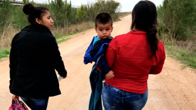 Central American immigrants walk after crossing the USMexico border to turn themselves in to Border Patrol agents on February 22 2018 near McAllen...