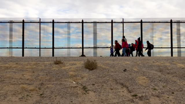 Central American immigrants walk along the border fence after crossing the Rio Grande from Mexico on February 01 2019 in El Paso Texas The migrants...