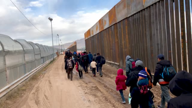 central american immigrants walk along the border fence after crossing the rio grande from mexico on february 01, 2019 in el paso, texas. the... - geographical border stock videos & royalty-free footage