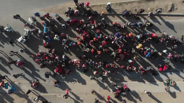 a central american migrant caravan waits for buses to take them to shelters in the mexican border city of tijuana - tijuana stock videos & royalty-free footage