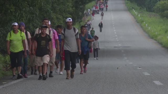 vídeos de stock e filmes b-roll de central american migrants crossing mexico towards the united states in a caravan resume their long trek walking about 12 hours to their next... - escolta