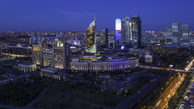 central asia, kazakhstan, astana, elevated view over the city center and central business district- day to night time lapse transistion - kazakhstan stock videos and b-roll footage