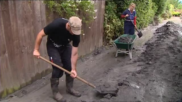 Central city residents shoveling silt from driveway caused by liquefaction and road cones marking large crack running along centre of street