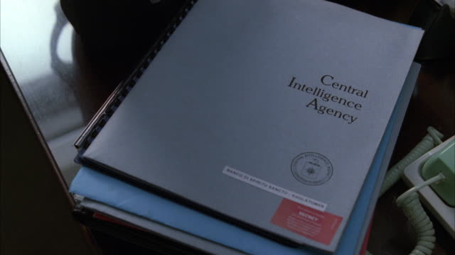 Central Intelligence Agency folders cover an office desk.