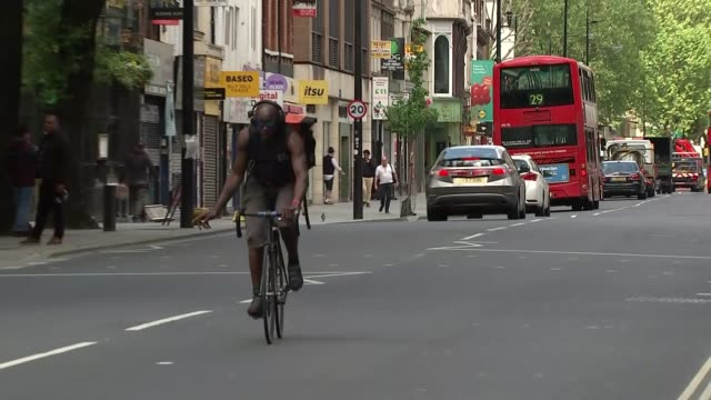 central london traffic and pedestrians during coronavirus lockdown; england: london: tottenham court road: ext two street wardens along quiet... - bicycle stock videos & royalty-free footage