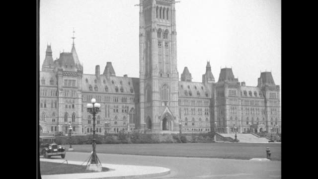 centre block's peace tower in bg leaves and top of wrought iron fence in fg / tower seen through ornamental fence in fg roofs of buildings / ws side... - オタワ点の映像素材/bロール