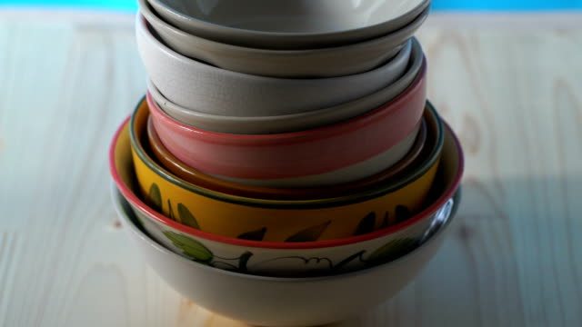 TU/Ceramic bowls stacked on wooden floor.