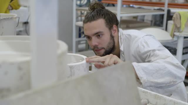 ceramic designer pouring clay into mold in workshop - 北ホラント州点の映像素材/bロール