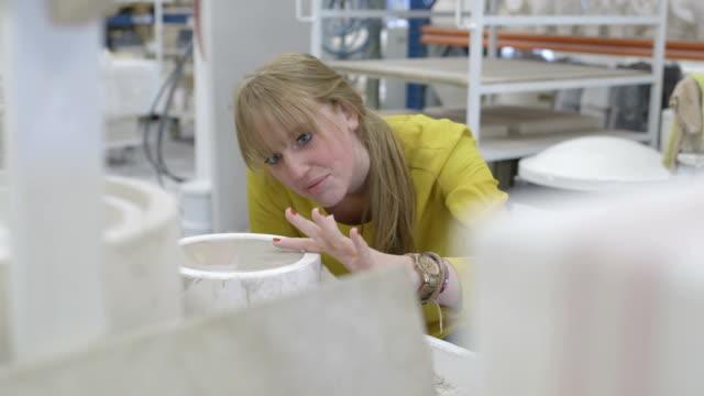 vídeos de stock e filmes b-roll de ceramic designer pouring clay into mold in workshop - só uma mulher de idade mediana
