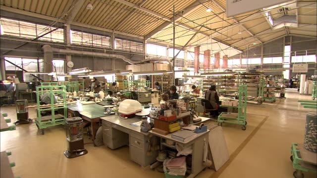 Ceramics factory workers paint pottery in Arita, Japan.