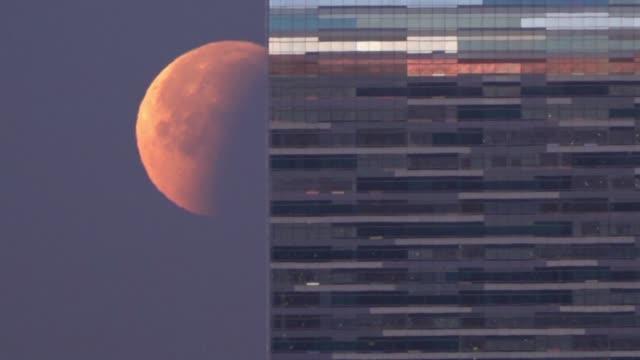 cercana grande y roja asi se vio la luna el miercoles en gran parte del planeta debido a un eclipse lunar particularmente raro - azul stock videos & royalty-free footage