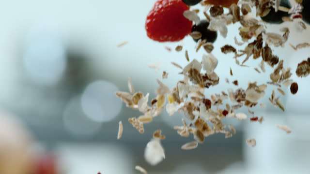 stockvideo's en b-roll-footage met slo mo cereals falling into a bowl full of yoghurt - dranken en maaltijden