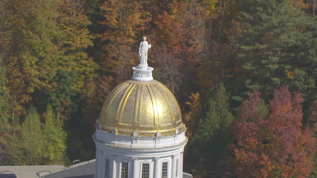 ws zo aerial pov ceres statue of vermont state house with autumn forest area / montpelier, vermont, unites states - vermont stock-videos und b-roll-filmmaterial