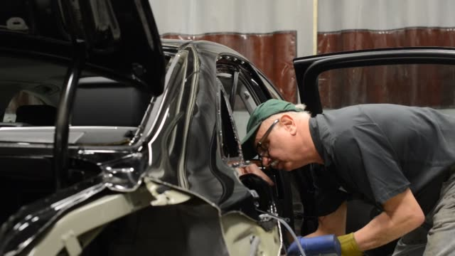 A certified aluminum auto body repair specialist prepares to install a new aluminum quarter panel on a 2013 Audi AG A8 L sedan at the Ultimate Paint...
