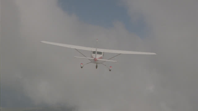 a-a cessna 172 thru clouds; land & water visible below at times - air vehicle stock-videos und b-roll-filmmaterial