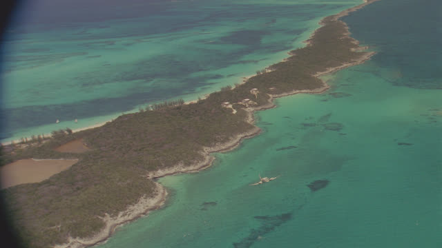 a-a cessna 310 twin low over narrow tropical island - aeroplane stock videos & royalty-free footage