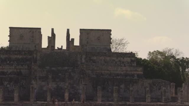 vídeos de stock e filmes b-roll de la ws zo chac mool statue atop wall near tourists walking past kukulkan pyramid at ancient mayan site chichen itza / yucatan, mexico  - por volta do século 7 dc
