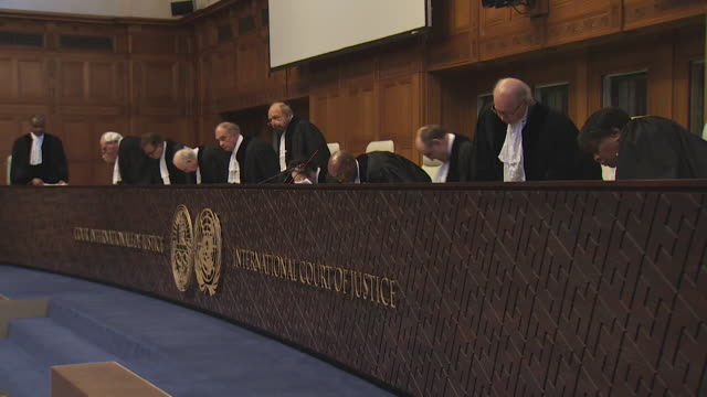 chagos campaigners at the international court of justice at the hague waiting for the verdict as to whether chagos will cease to be a british... - international court of justice stock videos and b-roll footage