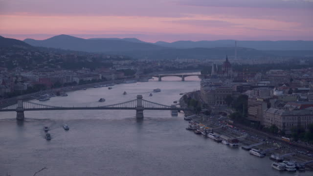 chain bridge with cityscape of budapest around danube river at evening from gellért hill - chain bridge suspension bridge stock videos & royalty-free footage