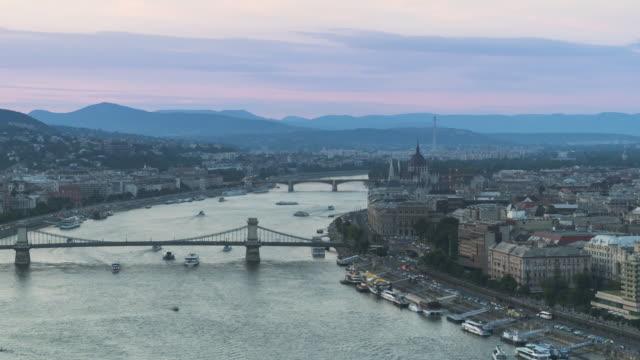 vidéos et rushes de tl: pont de la chaîne avec le paysage urbain de budapest autour du danube le soir à partir de gellért hill - culture hongroise
