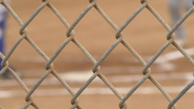 chain link fence and boys playing baseball in a little league game, seen through chainlink fencing. - recinzione video stock e b–roll