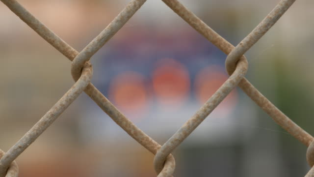 chain link fence and scoreboard and boys playing baseball in a little league game, seen through chainlink fencing. - slow motion - スコアボード点の映像素材/bロール