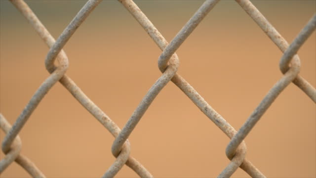 chain link fence at a little league baseball field, seen through chainlink fencing. - slow motion - chainlink fence stock videos and b-roll footage