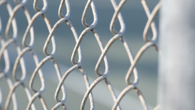 a chain link fence at a little league baseball game. - fence stock videos & royalty-free footage
