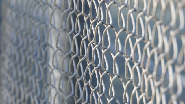 a chain link fence at a little league baseball game. - wire mesh fence stock videos & royalty-free footage