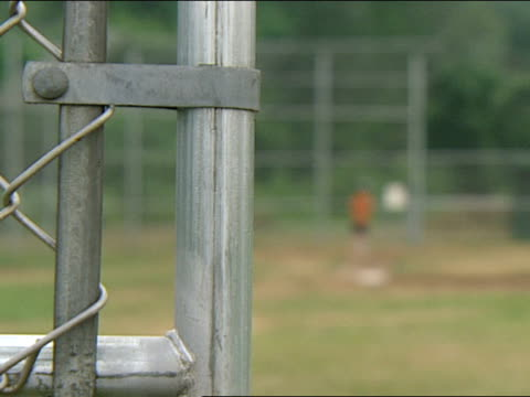 chain link fence at left of frame boy hitting baseballs in distance on right on little league baseball field rack focus on boy amp fence - youth baseball and softball league stock videos and b-roll footage