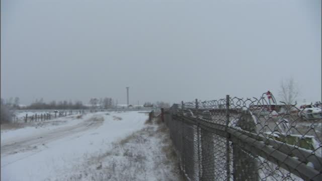 vídeos y material grabado en eventos de stock de a chain link fence encloses a salvage yard of aircraft wreckage. - eslabón