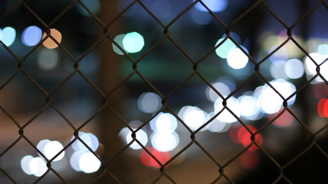 cu selective focus chain link fence with defocused traffic lights at night in background / los angeles, california, usa - 後ろボケ点の映像素材/bロール