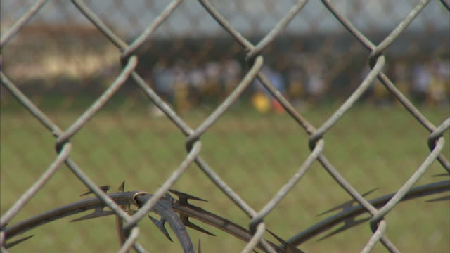 Chain link fence with men exercising in prison yard SOFT BG RACK FOCUS WS Unidentifiable inmates prisoners wearing football clothing exercising...