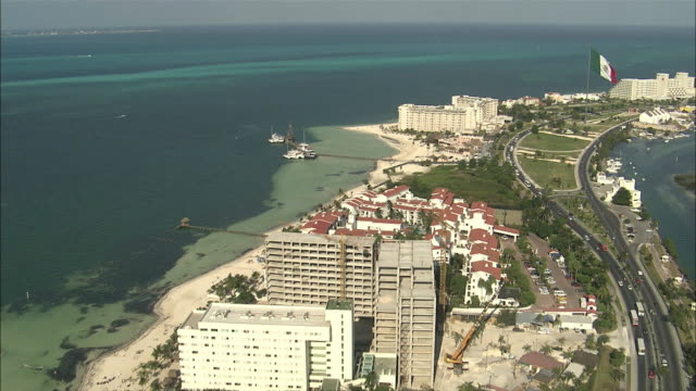 vídeos de stock, filmes e b-roll de aerial chain of barrier islands extending out into sea completely covered with resorts and condos, gigantic mexican flag blowing tall flag pole / cancun, quintana roo, mexico - quintana roo