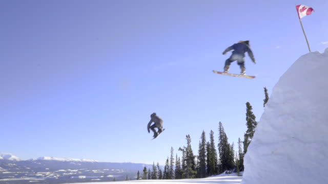 vídeos de stock, filmes e b-roll de a chain of snowboarders and skiers hitting a big air jump - cultura canadense