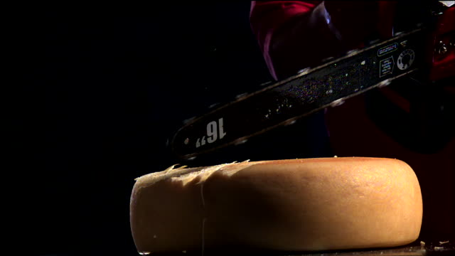 a chainsaw cuts a block of cheese. - käse stock-videos und b-roll-filmmaterial