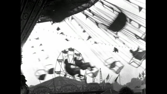b&w chair swing ride spinning at battersea park fun fair; 1953 - moving past stock videos & royalty-free footage