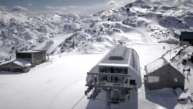 AERIAL Sessellift, die Skifahrer bergauf auf sonnige winter Tag